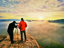 Photographying in wild nature. Nature photographer with big camera on tripod stay on summit rock. Listen to muse. Two men enjoy photographying in wild nature Royalty Free Stock Photography