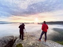 Photographying in wild nature. Nature photographer with big camera on tripod stay on summit rock. Listen to muse. Two men enjoy photographying in wild nature Royalty Free Stock Photos
