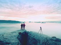 Photographying in wild nature. Nature photographer with big camera on tripod stay on summit rock. Listen to muse. Two men enjoy photographying in wild nature Stock Photo
