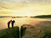 Photographying in wild nature. Nature photographer with big camera on tripod stay on summit rock. Listen to muse. Two men enjoy photographying in wild nature Royalty Free Stock Images