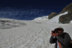 Photograping the glacier. Photographer taking a picture of the matterhorn from the Stockji glacier in Switzerland on a 2 day glacier crossing. In the background Royalty Free Stock Images