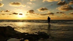 Photogrpaher and a Beautiful ocean sunset. Photogrpaher walking in a Beautiful ocean sunset and cloudy sky Stock Photos