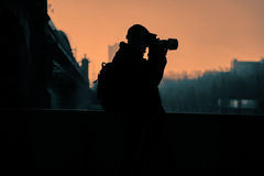 Photogrspher, hommes, sur le fond de lumière de coucher du soleil Photographie stock