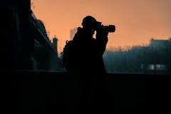 Photogrspher män, på solnedgångljusbakgrund Arkivbild