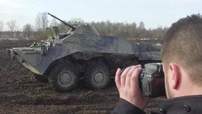 Photojournalist takes photographs of armored infantry vehicle in war zone stock video
