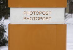 Bright orange machine in park, allowing you to take a photo. Photopost terminal in the park stock photography
