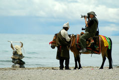 The photoreporter. Namtso lake is a very crowded destination in Tibet. There are so many visitors in summer - include the Chinese photographers. Thousands of Stock Photos