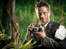 Photoreporter walking in the jungle with vintage camera Royalty Free Stock Photos