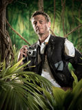 Photoreporter walking in the jungle with vintage camera Stock Photography