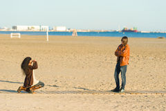 Photos on the beach. Women taking photographs of a teenager in autumn outfit Stock Photography
