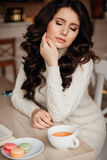 Photos of beautiful brunette with long hair and perfect makeup to wear knitted dress, eyes closed, touches the hand of Stock Image