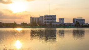 Photos Building River Town In Udon Thani, Thailand. Golden sky background. Sun during sunset Stock Photos