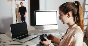 Photos capturées de révision de photographe féminin dans son appareil photo numérique au studio banque de vidéos
