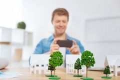 Skilled engineer taking photos of his works and feeling glad. Photos. Cheerful young skilled engineer feeling glad and taking photos of tiny trees after Royalty Free Stock Photos