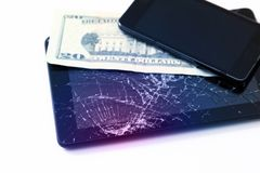 Photos of cracked display on a tablet, black cellphone and 20 dollars isolated on white. Tablet with damaged screen.  stock image