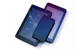 Photos of cracked display on a tablet and black cellphone isolated on white. Tablet with damaged screen.  stock images