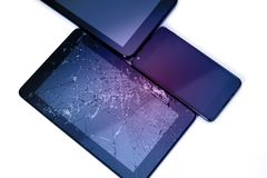 Photos of cracked display on a tablet and black cellphone isolated on white. Tablet with damaged screen.  royalty free stock photo