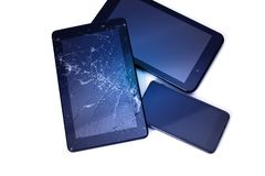 Photos of cracked display on a tablet and black cellphone isolated on white. Tablet with damaged screen.  stock photography