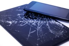 Photos of cracked display on a tablet and black cellphone isolated on white. Tablet with damaged screen.  stock image