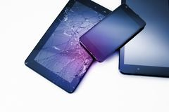 Photos of cracked display on a tablet and black cellphone isolated on white. Tablet with damaged screen.  stock photo