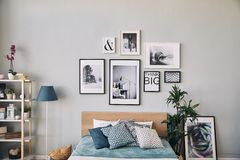 Photos de différentes tailles dans un cadre accrochant au-dessus du lit Intérieur moderne de chambre à coucher image libre de droits