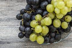 Photos des raisins noirs sur des photos de plancher, noires et vertes en bois de raisins dans le plat, les grands raisins noirs Photo stock