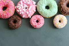 Photos of different donuts, free space for writing texts. Photos of different donuts. Assorted colorful donuts in glaze close-up, free space for writing texts royalty free stock photo