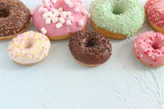 Photos of different donuts, free space for writing texts. Photos of different donuts. Assorted colorful donuts in pink, green, chocolate icing close-up, sweet stock images