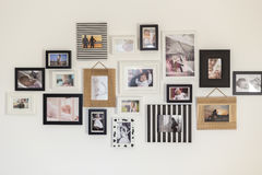 Photos of the family in various photo frames. White wall with photos of the family in various photo frames Royalty Free Stock Photo