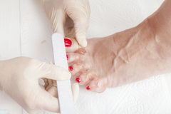 Photos of foot nail varnishing process, series of photos Stock Photos