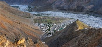 Photos from a great height on the Spiti Valley: near the river there is a small mountain village, the cliffs are lit by sunset ray. S of the sun, photo panorama Royalty Free Stock Photo