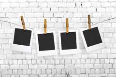 Photos hanging on a clothesline on brick wall background Stock Photography