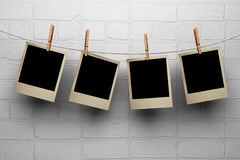 Photos hanging on clothespegs against a wall. Photos hanging on clothespegs against a white wall Royalty Free Stock Photo