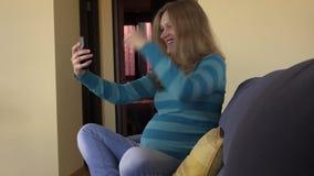 Photos mignonnes espiègles de selfie de prise de femme enceinte sur le smartphone banque de vidéos