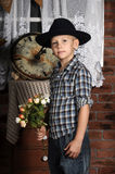 Boy in a hat and a bouquet of flowers Royalty Free Stock Image