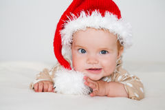 Photos of smiling young baby in a Santa Claus hat Stock Image