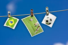 Photos of soccer ball, player and Brazil flag hanging. On clothesline Stock Photos