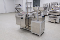 Photos sterile production area with the machine for the production of tablets and sorting. Photos sterile production area with stainless steel machine for the royalty free stock image