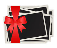 Photos which have been tied up by a red ribbon Stock Images