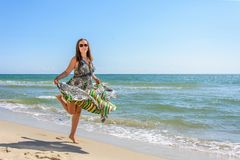 A pretty woman running along a black sea beach in a dress up against the sky royalty free stock images