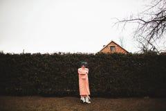 Photosession av en härlig flicka i en vit klänning på bakgrunden av gran-träd fäktar arkivbilder