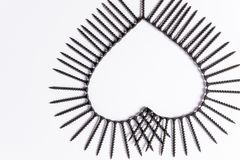 Black screws laid out in the shape of a heart on a white background. Photoset patterns arranged from black screws  on a white background in the form of a circle Royalty Free Stock Photos