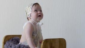 Photoshoot, младенец одетый в шляпе и платье сидит в деревянной коробке и представлять на камере сток-видео