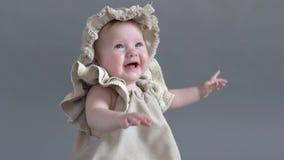 Photoshoot av lilla flickan i huvudbonad och klänning sitter, i träask och att posera på kamera arkivfilmer