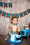 Photoshoot crush smashcake for a little boy gentleman. Decorated photozone with a wooden retro car and helium balloons. Happy. Birthday, 1 year stock image