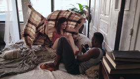 Photoshoot da manhã na cama A mulher atrativa nos pijamas esconde sob a cobertura, homem toma a foto na câmera velha imagens de stock royalty free