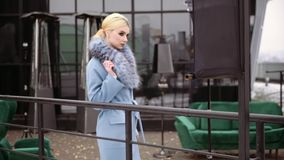 Photoshoot de la colección del abrigo de invierno para la cubierta de la revista Presentación modelo hermosa delante de a almacen de video