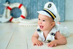 Photoshoot For A Boy Of One Year. Little Sea Captain, Sailor On Toy Ship With Steering Wheel. Sea Anchor And Lifebuoy On Gray Stock Photos