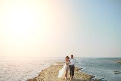 Photoshoot-Liebhaber in einem Hochzeitskleid auf dem Strand nahe dem Meer stockfotos