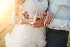 Photoshoot-Liebhaber in einem Hochzeitskleid auf dem Strand nahe dem Meer stockbilder